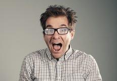 戴眼镜的年轻人张了他的嘴 免版税库存照片