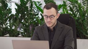 戴眼镜的年轻商人看膝上型计算机屏幕 股票录像