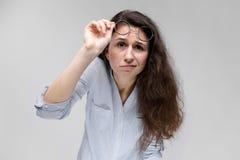 戴眼镜的年轻深色的女孩 她培养了她的玻璃 图库摄影