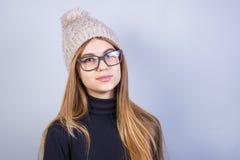 戴眼镜的年轻美女和冬天在灰色背景,很多干净的空间前面的帽子身分 免版税库存照片