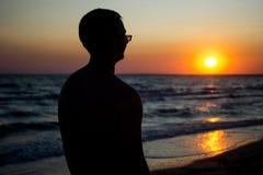 戴眼镜的愉快的年轻人看日落在海附近 库存照片