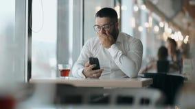 戴眼镜的有胡子的人看了在电话的好消息并且是愉快的 人商人愉快谈话在电话 股票视频