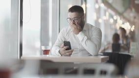 戴眼镜的有胡子的人看了在电话的好消息并且是愉快的 商人愉快谈话在电话 日志伽玛 股票视频