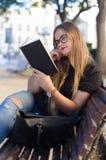 戴眼镜的甜白肤金发的女孩读在公园长椅的一本书 库存照片
