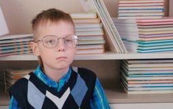 戴眼镜的疲乏的七岁的男孩坐在书中的地板 免版税库存照片