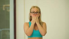 戴眼镜的白肤金发的妇女用她的手盖了她的嘴并且吹她的面颊 股票视频