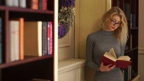 戴眼镜的美丽的女孩读书的半身观点的在图书馆里 影视素材