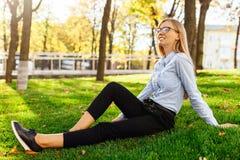 戴眼镜的美丽的少女微笑和享受热的坐绿色草坪 图库摄影