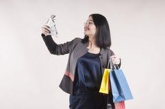 戴眼镜的美丽的年轻女实业家浅黑肤色的男人与购物的演播室的包裹,美元 免版税图库摄影