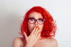 戴眼镜的美丽的震惊惊奇的妇女女孩,盖嘴用手 免版税库存图片