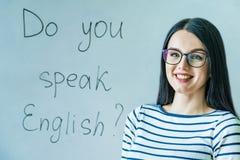 戴眼镜的美女和词您讲英语 库存照片
