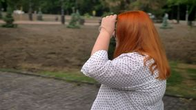 戴眼镜的肥胖姜女孩在阴沉的天气的公园走,微笑,侧视图 股票录像