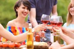 戴眼镜的青年人喝酒在桌上户外 免版税图库摄影