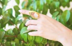 戴着一只大金戒指的妇女手 免版税库存照片