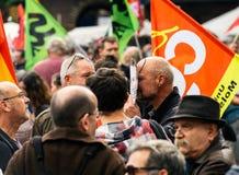 戴着伊曼纽尔macron面具的人在抗议 免版税库存图片