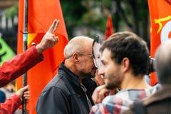 戴着伊曼纽尔macron面具的人在抗议 库存图片