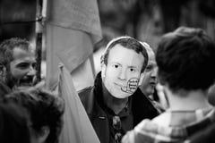 戴着伊曼纽尔macron面具的人在抗议 免版税库存照片