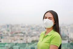 戴着保护面具的亚裔妇女反对PM 2 r ?? 免版税库存图片