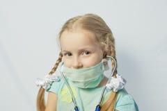 戴着医疗屏蔽的小白种人白肤金发的女孩 免版税库存图片