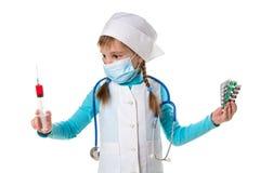 戴着医疗面具的女性护士拿着注射器和药片在手上,看注射器在右手 免版税库存图片