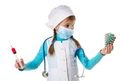 戴着医疗面具的女性护士拿着注射器和药片在手上,看药片板材在左边 库存图片