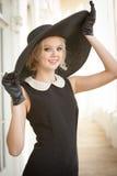 戴着大黑帽会议和手套的美丽的妇女 免版税库存照片