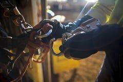 戴着手套的男性绳索通入手截去附有与锁carabiner入产业绳索通入harnes的RN笔画过线之字母 免版税库存照片