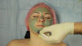戴着手套的男性美容师在一个客户s客户上的面孔把泥面具放有一把特别刷子的 股票录像