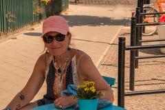 戴着有狗爪子纹身花刺的微笑的白种人妇女婴儿潮出生者一个桃红色帽子在她的右前臂坐在一蓝色桌outdoo 免版税库存图片