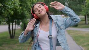 戴着红色耳机的美丽女孩欢快地跳跃,听音乐 股票录像