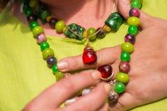 戴着美丽的宝石项链和金黄圆环与琥珀的妇女 免版税库存照片