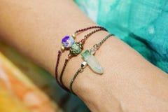 戴着自然石小珠镯子的女性手 免版税库存图片