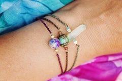 戴着自然石小珠镯子的女性手 免版税库存照片