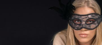 戴着黑面具的一名美丽的白肤金发的妇女的画象 方式 库存图片