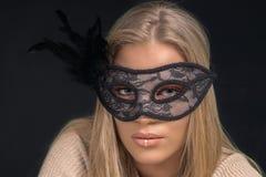戴着黑面具的一名美丽的白肤金发的妇女的画象 方式 免版税库存照片