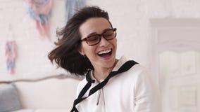 戴短发佩带的眼镜的年轻性感的深色的女孩,摆在为照相机,在英尺长度外面,有在她的风的 股票视频