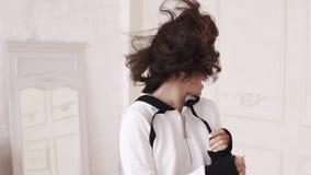 戴短发佩带的眼镜的年轻性感的深色的女孩,摆在为照相机,在英尺长度外面,有在她的风的 影视素材