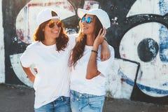 戴简单的T恤杉和太阳镜的模型摆在街道wa 免版税库存图片