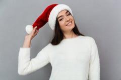 戴红色圣诞老人帽子的一个嬉戏的俏丽的女孩的画象 免版税图库摄影
