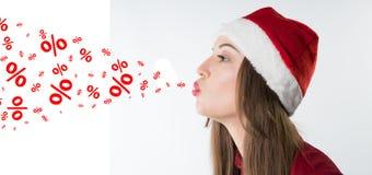 戴红色圣诞老人帽子的妇女吹折扣率 库存照片