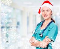 戴红色圣诞老人帽子的微笑的医生 免版税库存照片