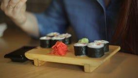 戴红色头发和眼镜的美丽的白种人女商人吃日本卷的在有筷子的一家餐馆 股票视频