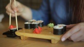 戴红色头发和眼镜的美丽的白种人女商人吃日本卷的在有筷子的一家餐馆 股票录像