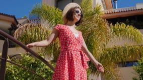 戴红色礼服、帽子和太阳镜的年轻美女站立在桥梁在有棕榈树的旅馆庭院里 ?motio 股票录像