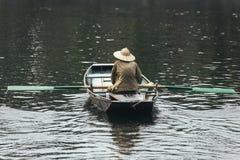 戴绿色衬衣和圆锥形帽子的划艇人坐在有桨的一条小船在河在背景中 免版税库存图片