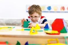 戴获得与大厦的乐趣和创造几何图的眼镜的愉快的孩子男孩,学会数学和几何 库存图片