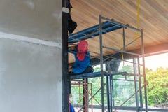 戴蓝色长袖的T恤杉和红色帽子的亚裔女工是修筑在大厦里面的墙壁的脚手架 库存照片