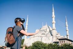 戴虚拟现实眼镜的一个旅客 真正旅行的概念环球 在背景中蓝色 库存图片