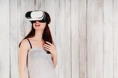 戴虚拟现实眼镜的一个相当少妇,激动 免版税库存照片