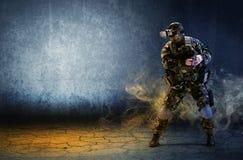 戴虚拟现实眼镜的一位战士拿着一把手枪在喂 免版税库存照片